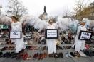 Activistas medioambientales vestidos de ángeles junto a miles de pares de zapatos colocados en la Plaza de la República de París, Francia.
