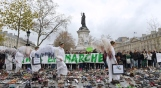 """Women dressed as angels holds signs at the Place de la Repubique where hundreds of pairs of shoes were places earlier, on November 19, 2015, in Paris, on the eve of the official opening of the COP21 UN Conference on climate in the French capital. The shoes were placed as part a symbolic and peaceful rally called by the NGO Avaaz or Voice """"Paris sets off for climate"""". AFP PHOTO / MIGUEL MEDINA / AFP / MIGUEL MEDINA (Photo credit should read MIGUEL MEDINA/AFP/Getty Images)"""